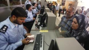 Policial palestino verifica passaportes após a abertura da passagem de Rafah, neste sábado 28 de maio.