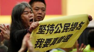 2017年3月19日香港三名特首竞选人辩论之际,泛民主派议员梁国雄举牌抗议,呼吁特首普选。