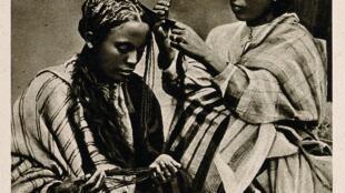 Reproduction d'une photographie d'une femme malgache en coiffant une autre.