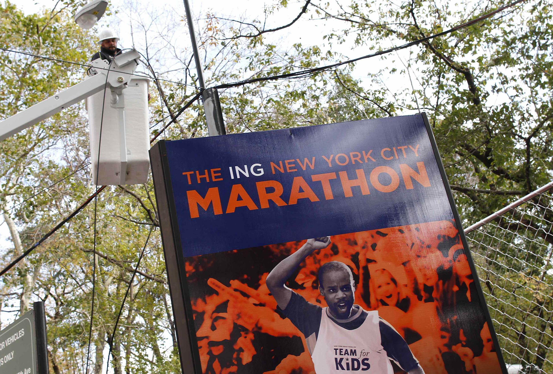Operário verifica linhas de energia elétrica próximo a um anúncio da famosa maratona de Nova York. Prova está cancelada.