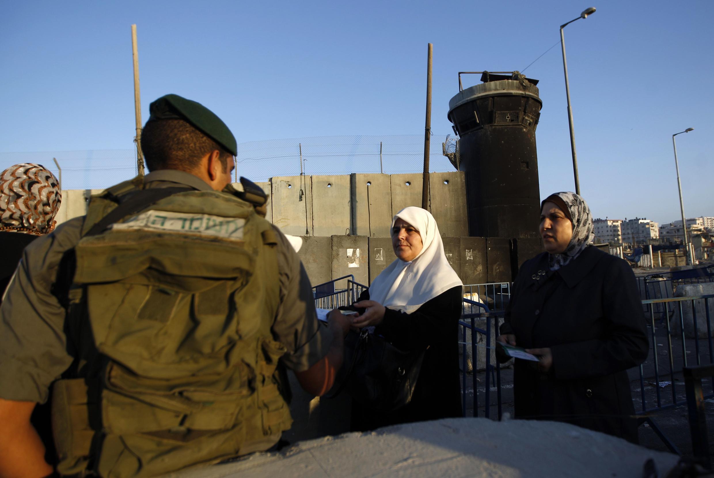 Mulher palestina mostra documentos a policial israelense para poder entrar em Jerusalém para o Ramadã