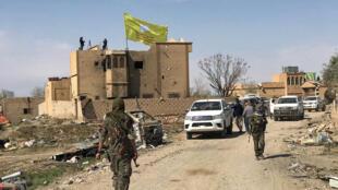 Bandeira das Forças Democráticas Sírias é vista sobre um prédio de Baghuz, na Síria, que foi definitivamente tomada do grupo Estado Islâmico neste sábado (23/03/2019).