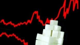 Unos azucarillos y una pantalla con la curva de cotización del azúcar en 2012, en una imagen tomada en París el 10 de enero de 2013