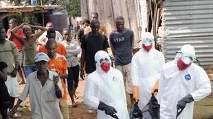 Wafanyakazi wa idara ya afya wakibeba muili wa mtu aliefariki kutokana na Ebola, Septemba 11 mwaka 2014.