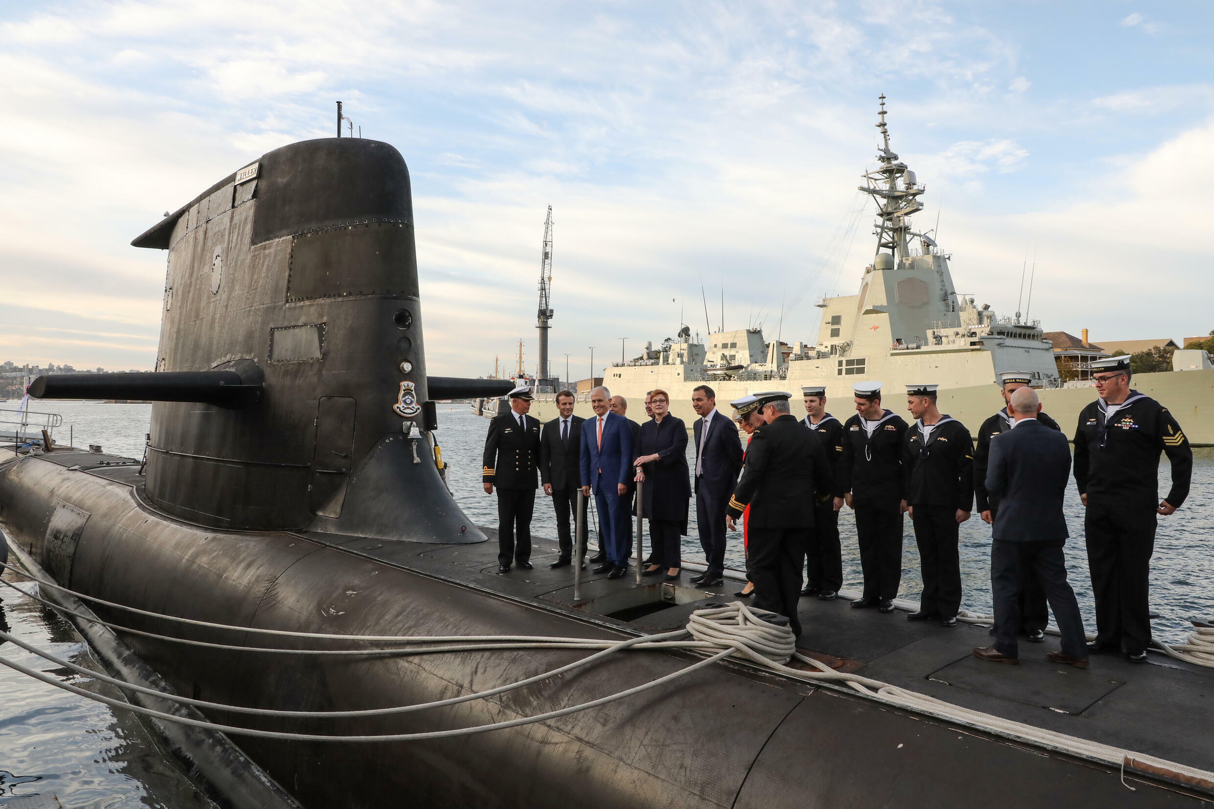 French President Emmanuel Macron (2nd L) and former Australian prime minister Malcolm Turnbull (3rd L) stand on the deck of a Collins-class submarine in Sydney in May 2018 -- reports say that an expected security deal with the United States and Britain could derail Australia's plans to purchase French submarines