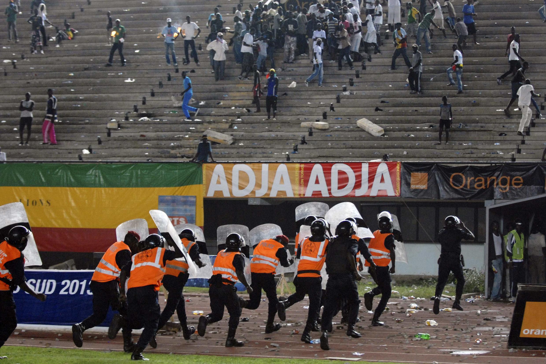 Police officers run with shields as Senegalese football fans throw rocks at them at Leopold Sedar Senghor stadium in Dakar