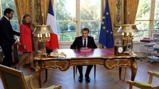 Президент Макрон подписывает закон в присутствии министра юстиции Николь Беллубе и официального представителя правительства Кристофа Кастанера, 15 сентября 2017.