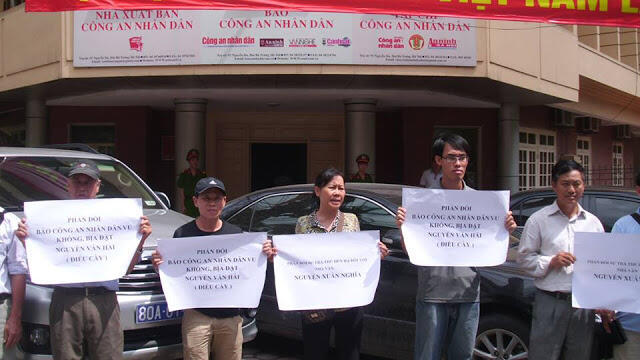 Gia đình blogger Điếu Cày biểu tình trước cửa toà soạn báo Công an Nhân dân (http://lenguyenhong.blogspot.fr)