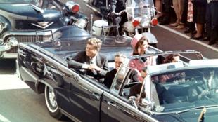 Le président américain F. Kennedy salue la foule depuis sa décapotable, à Dallas, quelques minutes avant son assassinat, le 22 novembre 1963.