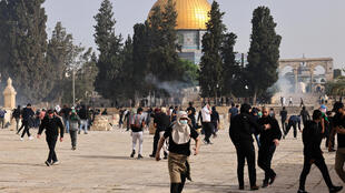 Palestinians run for cover from tear gas fired by Israeli security forces at Jerusalem's Al-Aqsa mosque compound on May 10, 2021