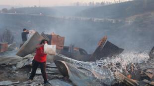 Moradora tenta apagar incêndio que destruiu sua casa em Valparaíso, nesta segunda-feira 2 de janeiro de 2017.