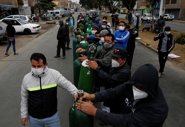 Fila de espera para recarregar cilindros de oxigênio em Lima.