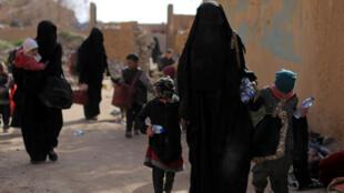 Des familles de combattants du groupe Etat islamique marchent pendant qu'elles se rendaient dans le village de Baghouz, dans la province de Deir Ezzor, le 12 mars 2019.