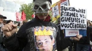 """Активист антиядерной манифестации в Париже с плакатом: """"Самоубийцы, закройте ваши глотки и ваши АЭС"""""""