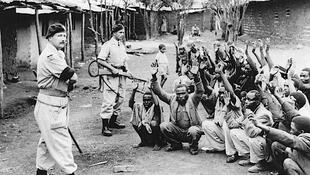 Wasu turawan mulkin mallakar Birtaniya a Kenya, yayin da suke gadin wasu da ake zargin zama 'yan kungiyar Mau Mau mai nemarwa kenya 'yanci, a tsakanin shekarun, 1952 zuwa 1960.