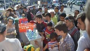 Distribuição de comida aos refugiados que chegam na estação de trem de Munique.