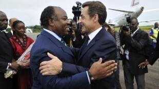 L'ancien président français, Nicolas Sarkozy (d.) accueilli par le président gabonais, Ali Bongo à l'aéroport de Franceville, le 24 février 2010.