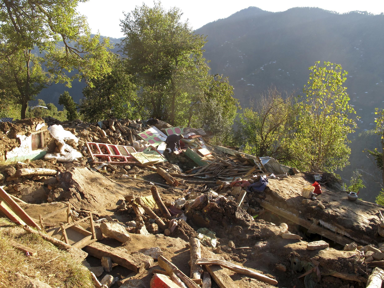 Dans le district de Shangla, à Belliy Baba, un homme fouille les décombres de sa maison à la recherche d'effets personnels, ce mercredi 28 octobre 2015.