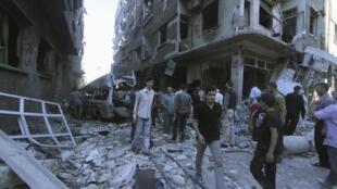 Moradores de Duma, perto de Damasco, caminham entre os escombros, após lançamento de foguetes do regime sírio.