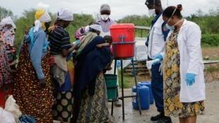 Des Burundais se lavent les mains, à titre préventif contre le coronavirus Covid-19, à l'arrivée de leur rapatriement à Gatumba, à la frontière avec la République démocratique du Congo, au Burundi, le 18 mars 2020.