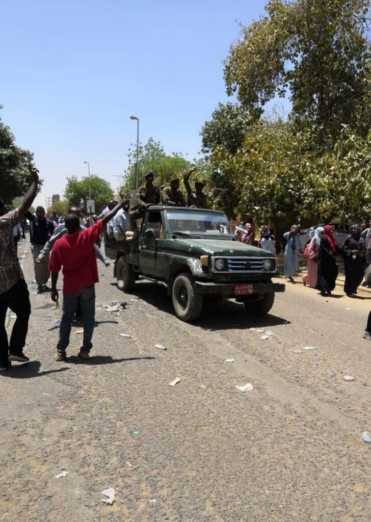 Sudanese protesters flash the victory sign at a passing military vehicle as they take part in a demonstration near the military headquarters in Khartoum on 8 April 2019.