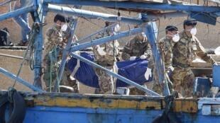 Des soldats transportent le corps d'une victime repêchées dans le port de Lampedusa, le 6 octobre 2013.