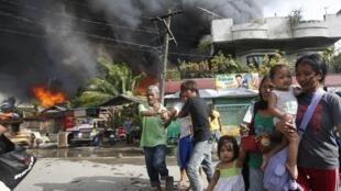 Des habitants se retrouvent dans la rue après des combats entre les soldats du gouvernement et les rebelles musulmans du Front Moro, à Zamboanga, le 12 septembre 2013.