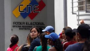 Eleitores venezuelanos aguardam diante de escritório do Conselho Nacional Eleitoral (CNE) nesta sexta-feira (24).