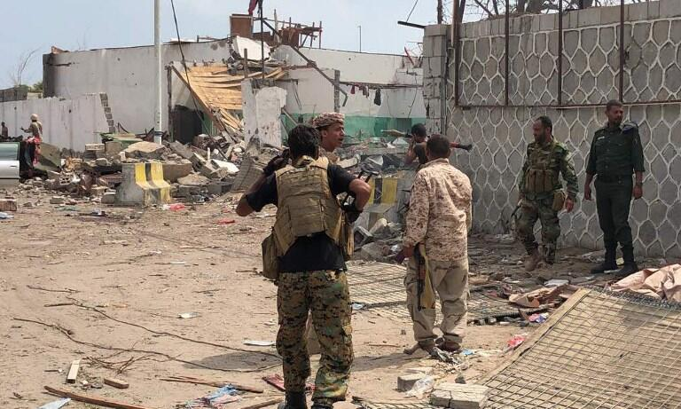 Des forces de sécurités yéménites et des habitants d'Aden observent le lieu d'une attaque suicide à la voiture piégée, le 5 novembre 2017.