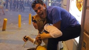 Des manifestants au milieu des gaz lacrymogènes, lors d'une manifestation mettant en cause la responsabilité du gouvernement turc suite à l'attentat de Suruç.