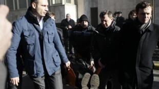 Виталий Кличко помогает нести носилки с раненым во время столкновений в Киеве 18/02/2014