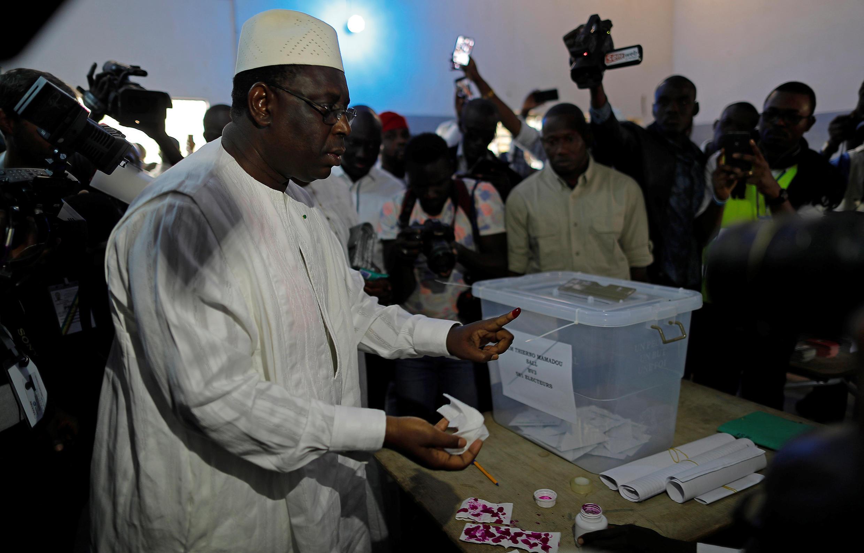 Le président sortant Macky Sall, candidat à sa réélection, dépose son bulletin dans l'urne à Fatick, sa ville natale, le 24 février 2019, dans l'ouest du Sénégal.