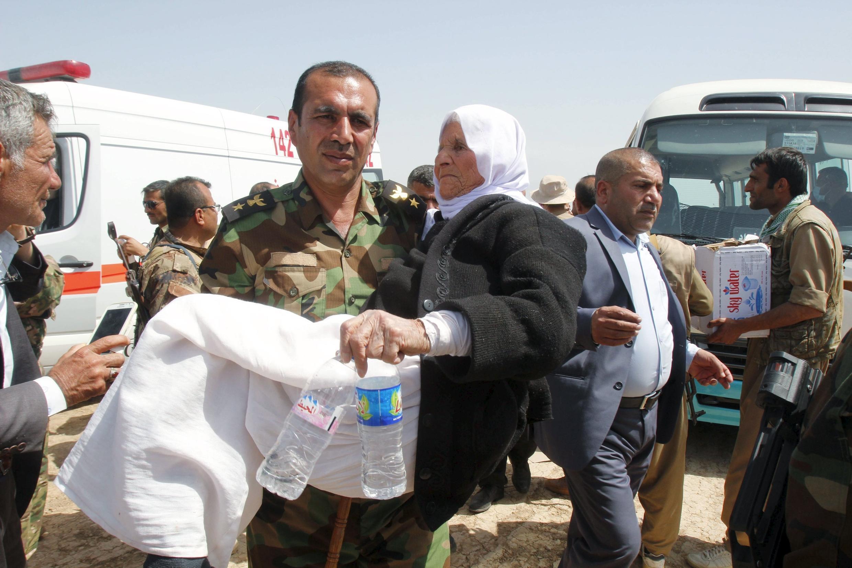 Mulher é carregada por soldado curdo depois de ser libertada.