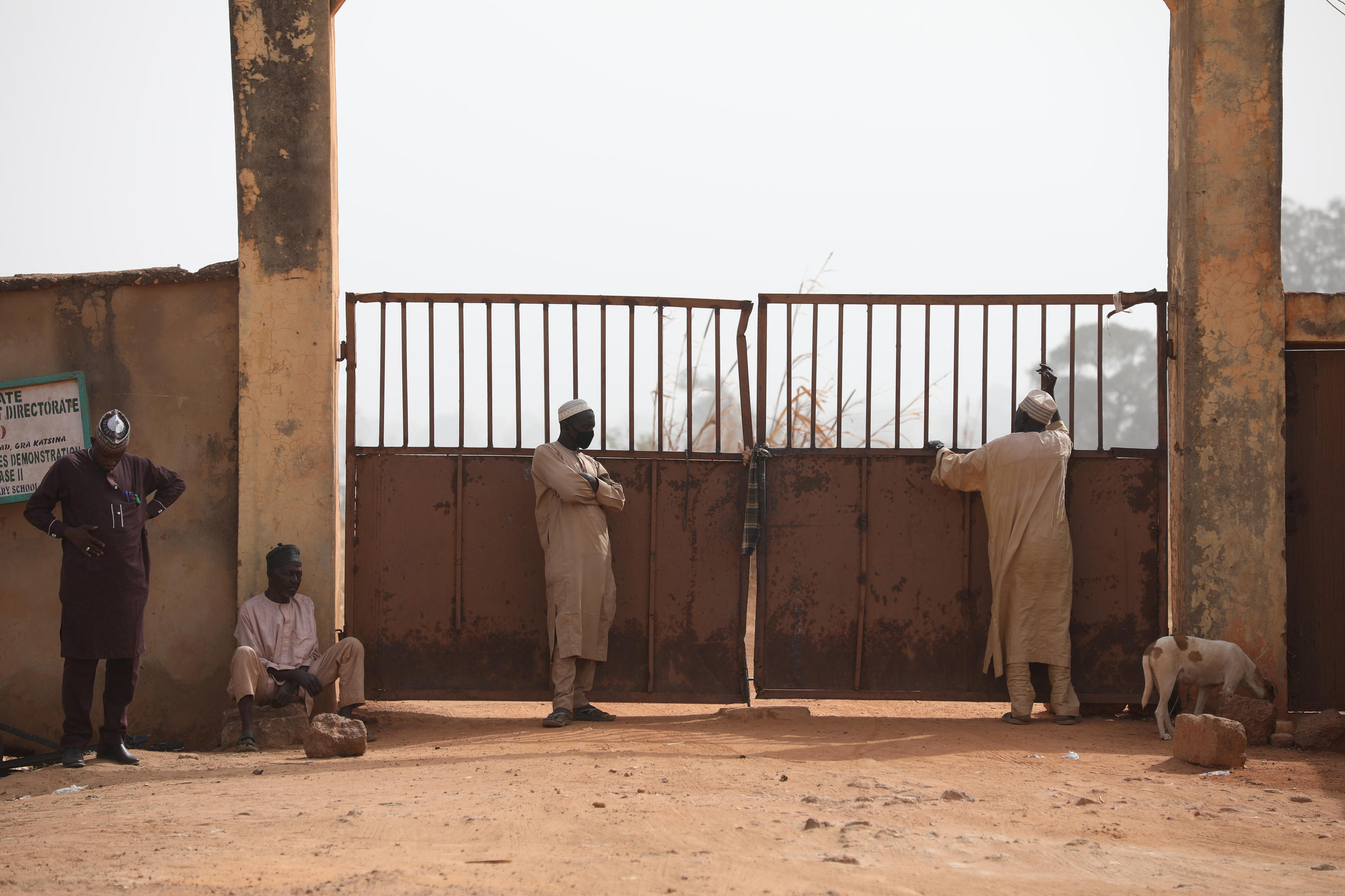 Parents wait outside the Government Science Secondary School in Kankara, in northwest Nigeria on December 16, 2020. Boko Haram claimed the abduction of hundreds of schoolboys from the school, more than 300 of whom have since been released