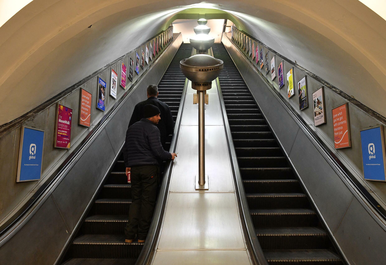 Un viajero utiliza las escaleras mecánicas en la estación Clapham North del metro de Londres el 17 de marzo de 2020
