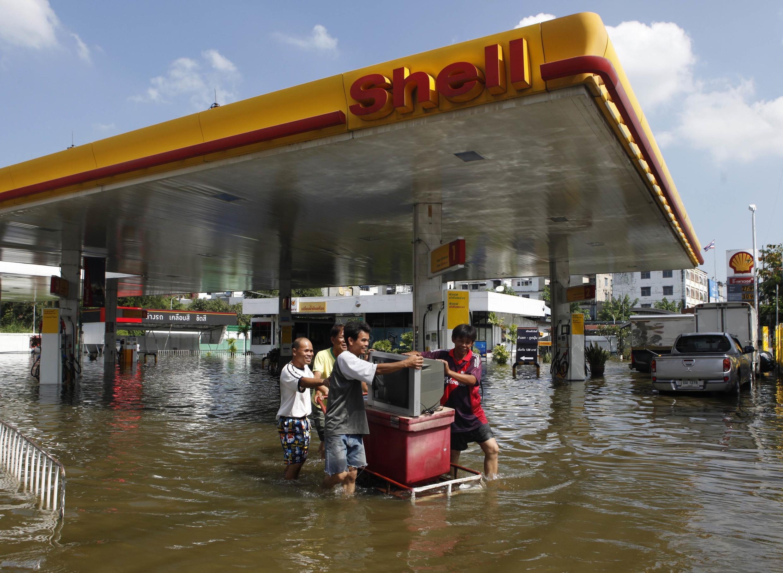 Moradores transportam eletrodomésticos após enchentes em Bangkok, na Tailândia.