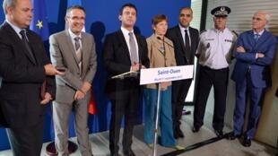 Le ministre français de l'Intérieur, Manuel Valls (c) au commissariat de Saint-Ouen, le 11 septembre 2012.