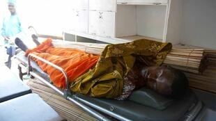 A body, suspected to be of a supporter of Cellou Dalein Diallo, lies on a stretcher in Guinea's capital Conakry
