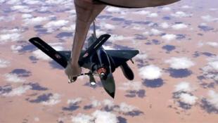 Un Mirage 2000D français est ravitaillé en vol au-dessus de l'Afrique.
