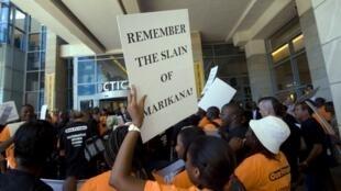 Des manifestants campent devant l'entrée du 19e Salon annuel des mines au Cap, le 5 février 2013. Sur la pancarte, il est écrit: «Souvenez-vous des morts de Marikana !»