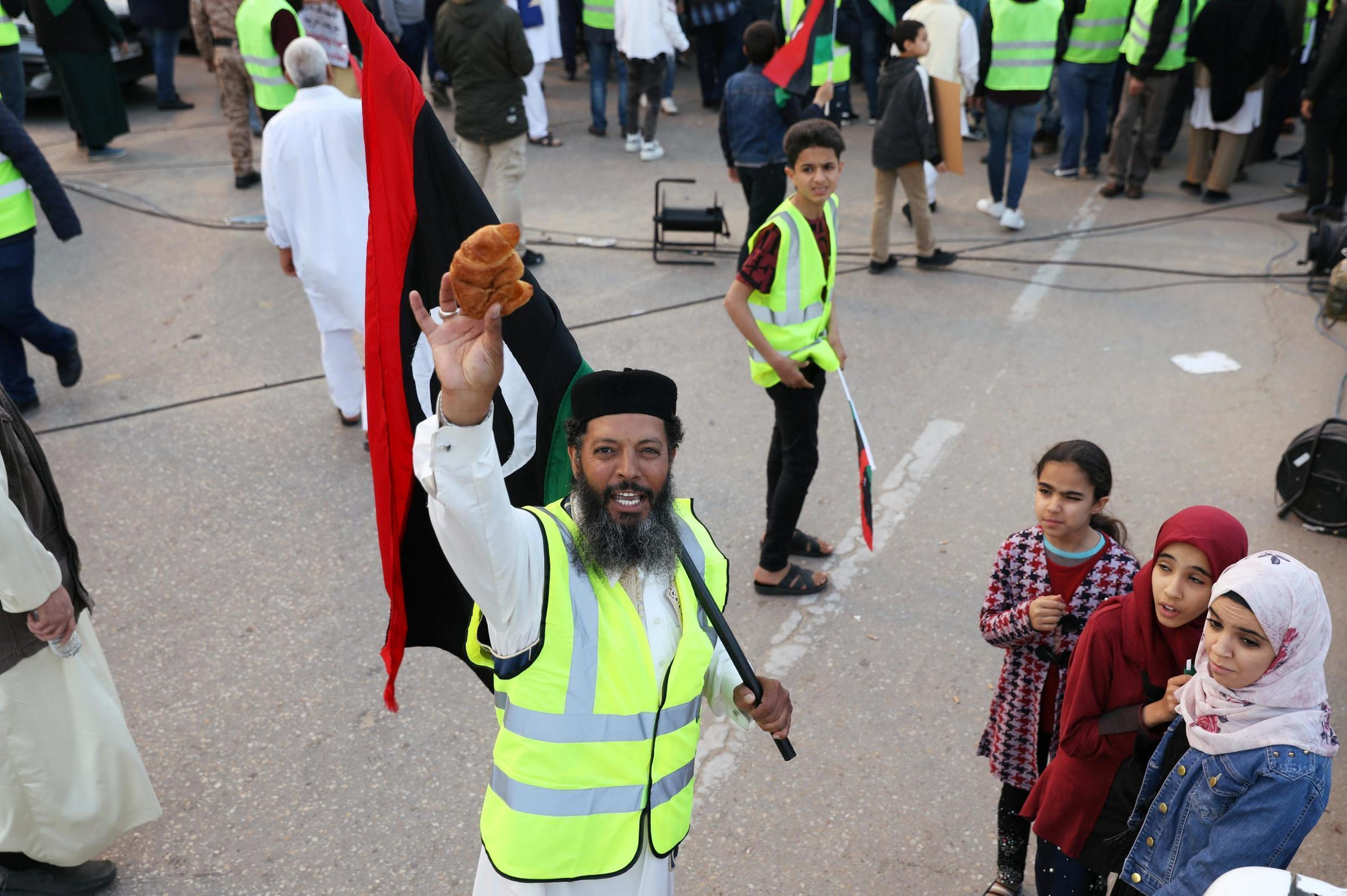 A Libyan protester holds a croissant as he attends a demonstration to demand an end to Khalifa Haftar's offensive against Tripoli in Martyrs Square in central Tripoli, April 19, 2019.