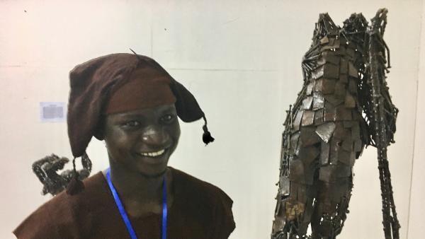 Le jeune sculpteur Hamidou Koumare et l'une de ses œuvres.
