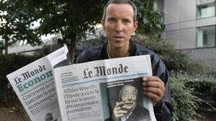 Gérard Davet, the journalist whose article prompted the investigation,  poses with a copy of the Le Monde