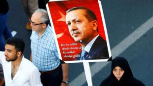 Женщина с портретом президента Турции Эрдогана во время манифестации 15 июля 2017. Надпись на плакате гласит: «Мы здесь, чтобы служить нации, а не повелевать ею».