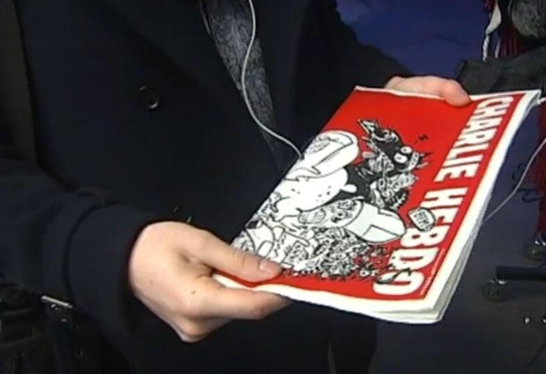 Un cliente con un ejemplar de la edición de Charlie Hebdo del 25 de febrero.
