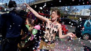 Активистка Femen перед зданием, где проходит первомайский банкет Нацфронта, 1 мая 2016 г, Париж