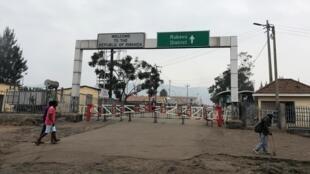 Congoleses caminham perto das barreiras do portão no ponto de passagem da fronteira com o Ruanda após o seu fechamento.