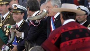 El presidente de Chile, Sebastián Piñera, toma cidra del cuerno de una vaca durante un desfile militar en Santiago, el 19 de septiembre de 2011.