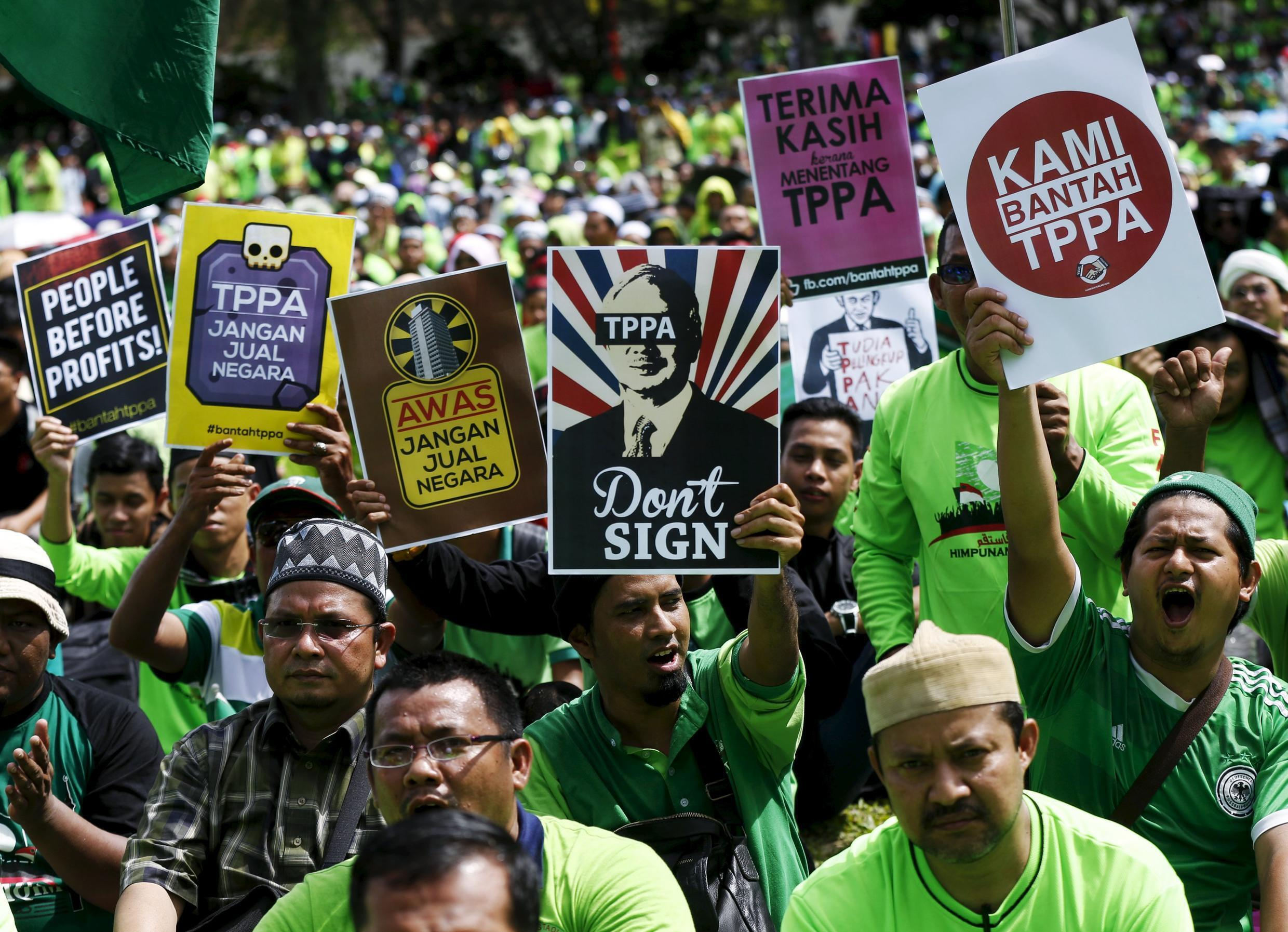 Protestors wave placards at a rally against the Trans Pacific Partnership (TPP) just days before parliament is due to open a debate on the free trade pact in Kuala Lumpur