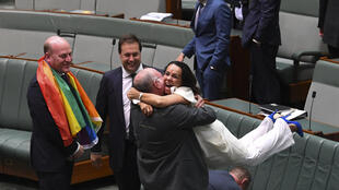 El legislador liberal Warren Entsch levanta en brazos a su par Linda Burney celebrando la adopción del matrimonio homosexual, el 7 de diciembre de 2017 en Canberra.